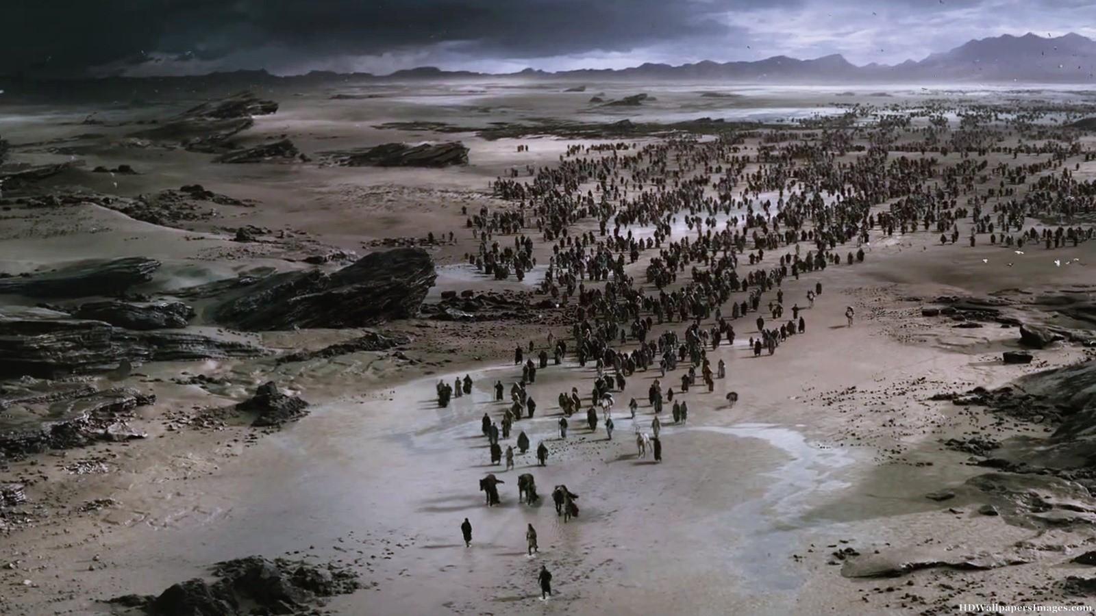Hundreds of tiny figures of people walking across a barren landscape.